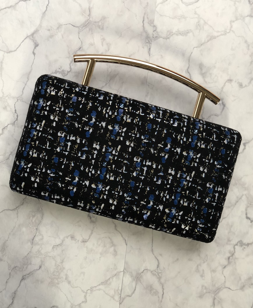Tweed like handle clutch bag